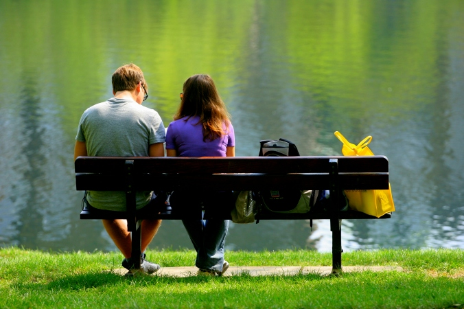 casal_banco_costas_sol_grama_lago
