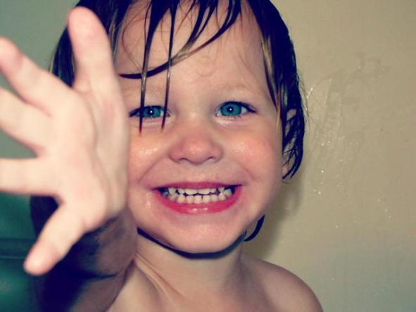 bebe-loiro-rindo-sorriso-olho-verde-cabelo-molhado-mao-direita-levantada