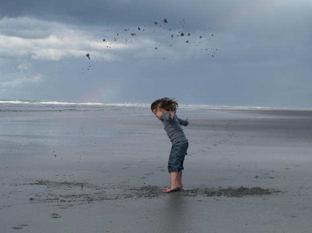 crianca-areia-praia-cabelos-longos-ceu-nuvens